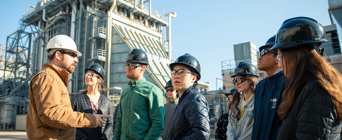 students wearing hardhats getting a tour of an industrial plant