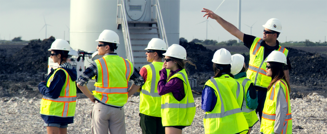 a group of students getting a tour of a wind farm